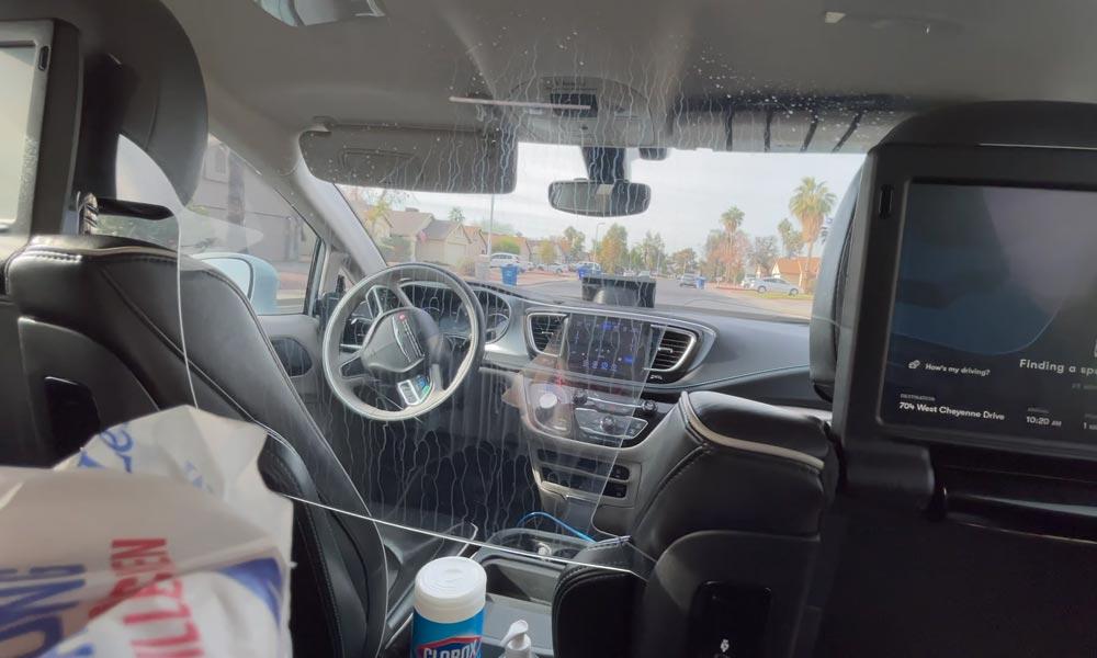 Der Innenraum eines Waymo One Taxis vom Rücksitz aus fotografiert. Niemand sitzt am Steuer, das Lenkrad bewegt sich wie von Geisterhand.