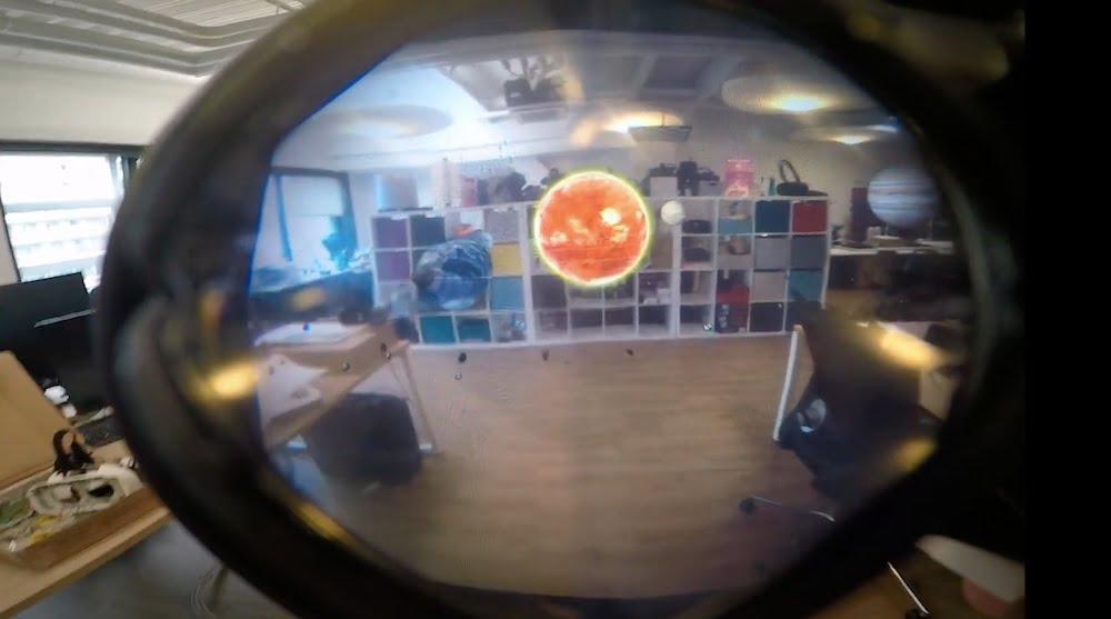 Man sieht durch die Gläser eine Brille ein hochauflösendes Video, das die normale Raumumgebung und darin ein digitales Sonnensystem zeigt.