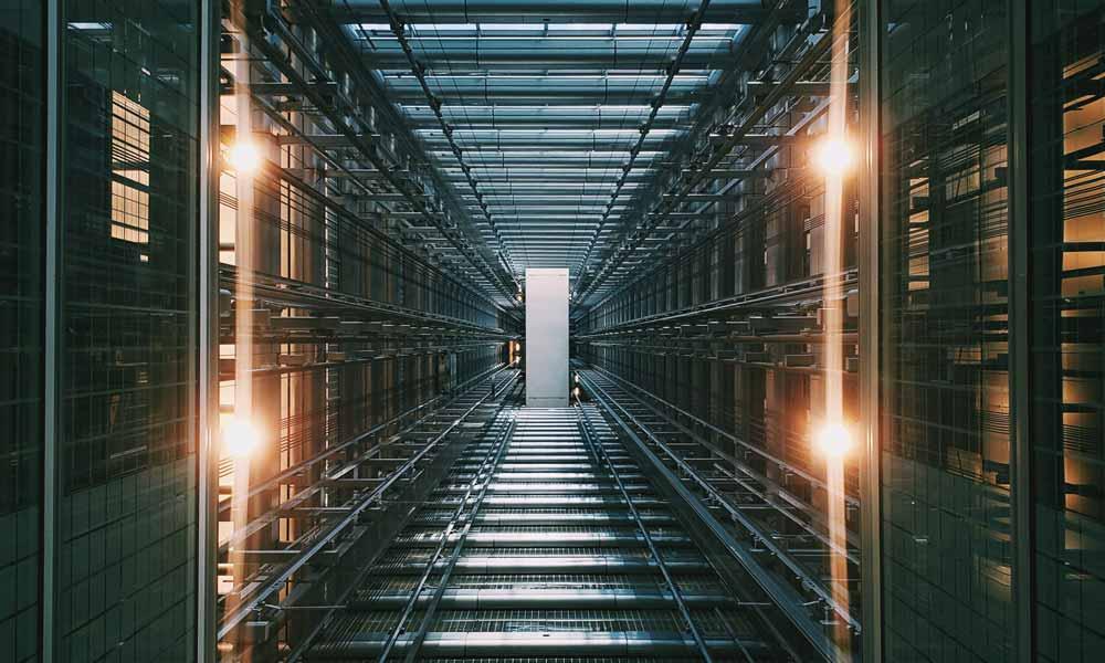 Ein langer Gang in einem Serverraum mit vielen Computern. Das Bild ist sehr dunkel und düster.